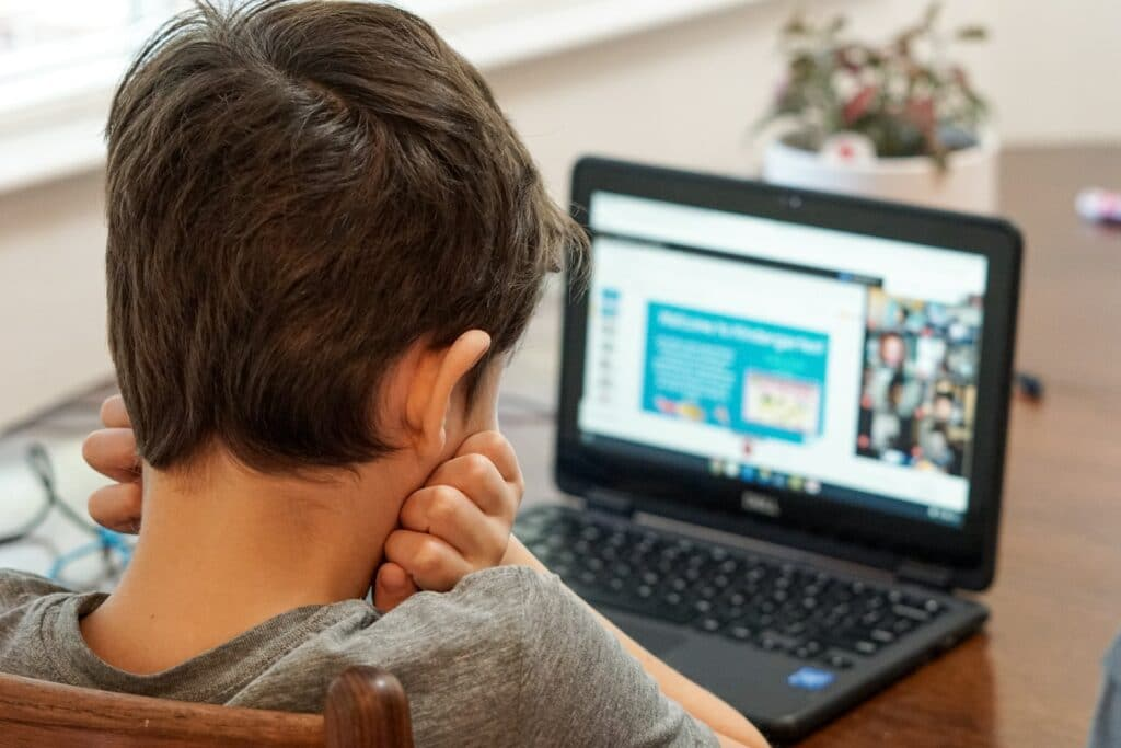 A child photographed from behind looking at their online class.